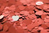 valentine concept: red metallic heart shaped confetti photographed with a narrow depth of field