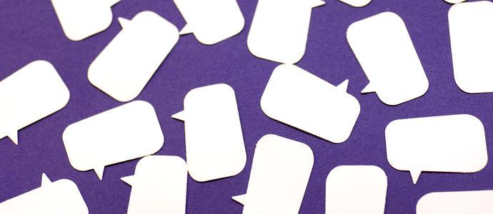 a random arrangement of speech bubble shapes cut out of paper